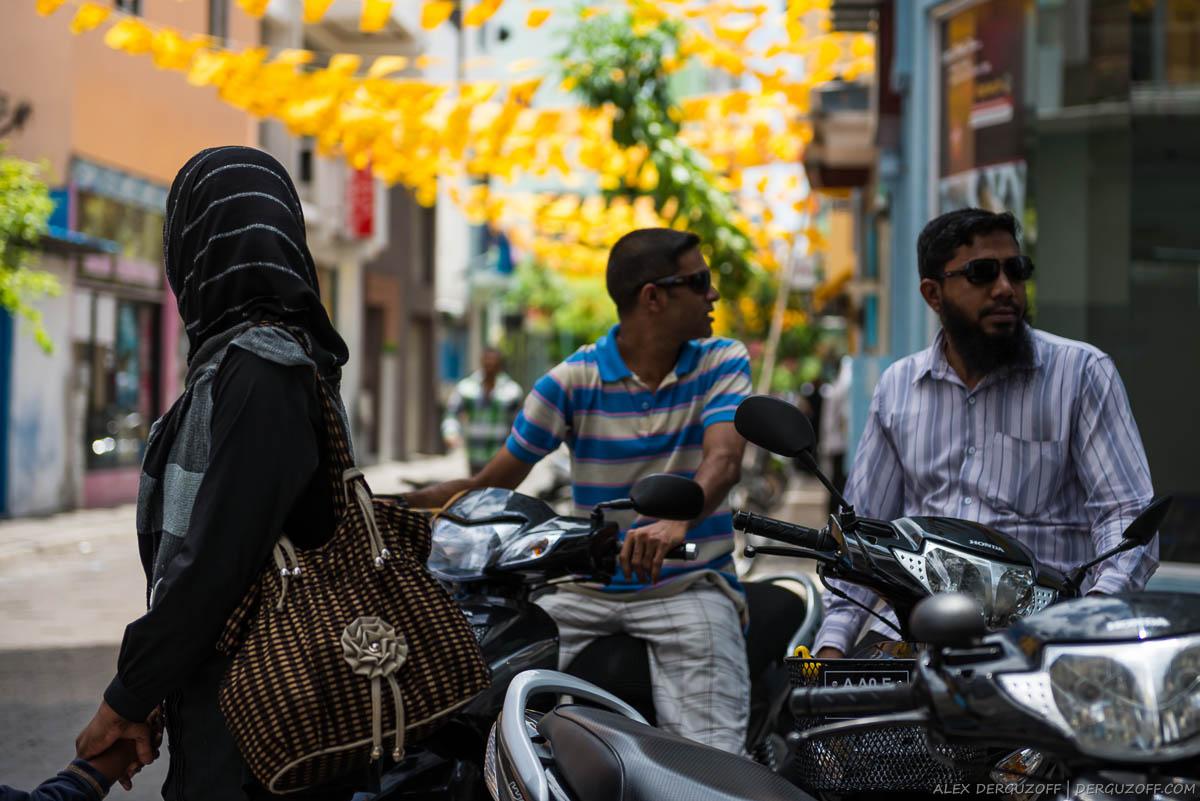 Девушка в парандже и мужчины на мопедах Мальдивы
