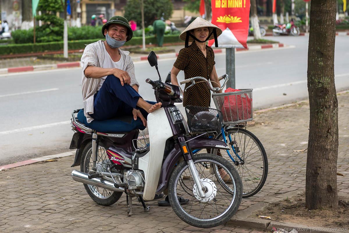 Мужчина в пробковом шлеме на мопеде и женщина в соломенной шляпе с велосипедом