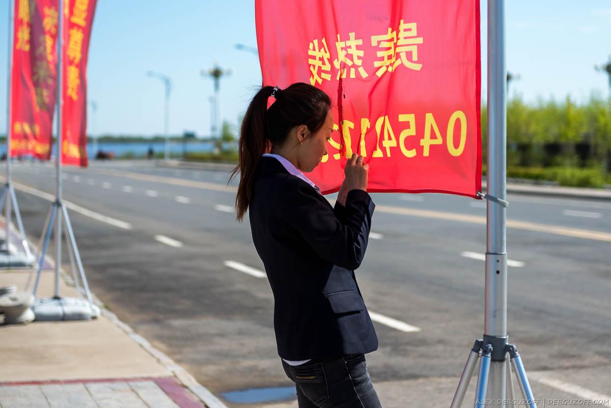Девушка зашивает красный флаг Китай Фуюань