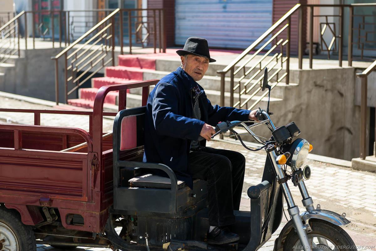 Пожилой китаец на мотоцикле
