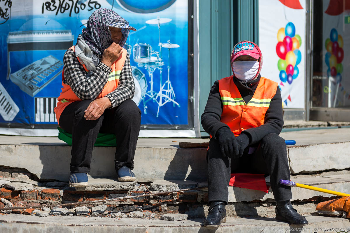Дворники сидят на тротуаре Китай Фуюань
