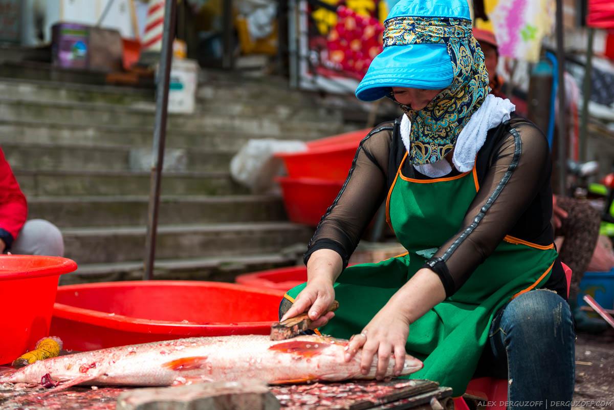 Китаянка чистит рыбу