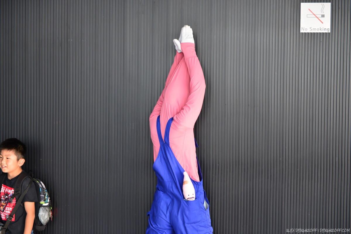 Мужчина в яйцеголовом костюме стоит лицом к стене